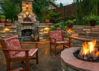outdoor living space with chairs, fireplace, and fire pit